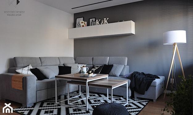 szary salon minimalistyczny, drewniany stolik z białymi nogami, biały dywan w czarne romby