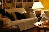 biała narzuta na sofę, drewniany stolik, złota lampa stołowa