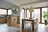 drewniana podłoga, beżowa lampa wisząca, biała cegła, lampa wisząca z białym abażurem