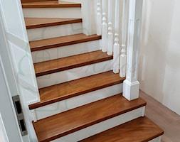 Schody drewniane aformozja z białymi tralkami - zdjęcie od STOLARKA MIKOS