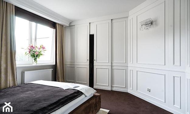 biała lamperia na ścianie, brązowa wykładzina, brązowa narzuta