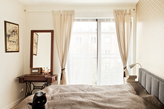sypialnia w odcieniach beżu, biurko ze starej maszyny do szycia, beżowa narzuta na łóżko, kremowe załony