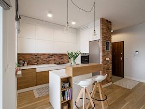 RYDYGIERA - Średnia otwarta biała kuchnia dwurzędowa z wyspą z oknem - zdjęcie od Qbik Design