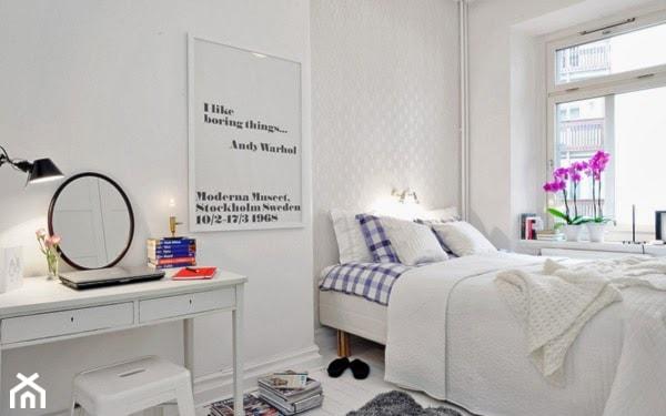 szary dywanik, okrągłe lustro, metalowy taboret, biała narzuta na łóżko