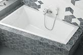 nieregularna wanna zabudowana w nowoczesnej szarej łazience
