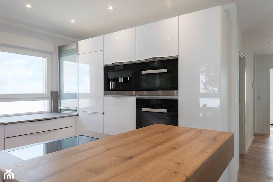 RAUVISIO crystal - Duża otwarta biała kuchnia w kształcie litery g w aneksie z oknem, styl nowoczesny - zdjęcie od REHAU