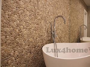 Beżowe otoczaki na ścianie w łazience