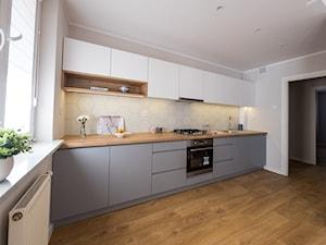 Mieszkanie na sprzedaż - Duża otwarta biała beżowa kuchnia jednorzędowa w aneksie z oknem, styl skandynawski - zdjęcie od Amicus Design