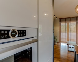 Bia%C5%82a+kuchnia+w+ciep%C5%82ym+minimalistycznym+salonie+-+zdj%C4%99cie+od+Vibo+Studio+%7C+architektura+%26+projektowanie+wn%C4%99trz