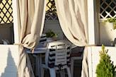 biała altana z kremowymi zasłonami, białe meble ogrodowe