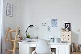 drewniana drabina, białe biurko, czarna lampa biurowa, biały fotel