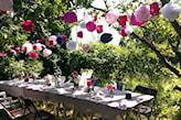 różowe lampiony w ogrodzie nad stołem
