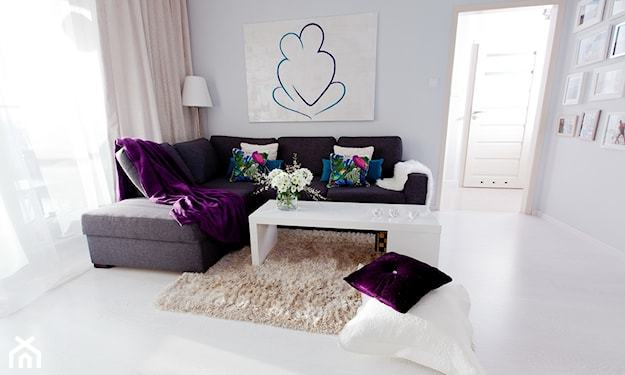 grafitowa sofa, fioletowa narzuta, zasłony w odcieniu pudrowego różu, beżowy dywan z długim włosiem