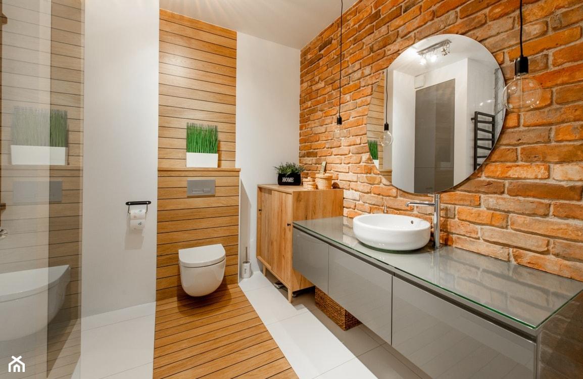 cegła naturalna, okrągłe lustro, szara szafka podumywalkowa, drewniana szafka w łazience