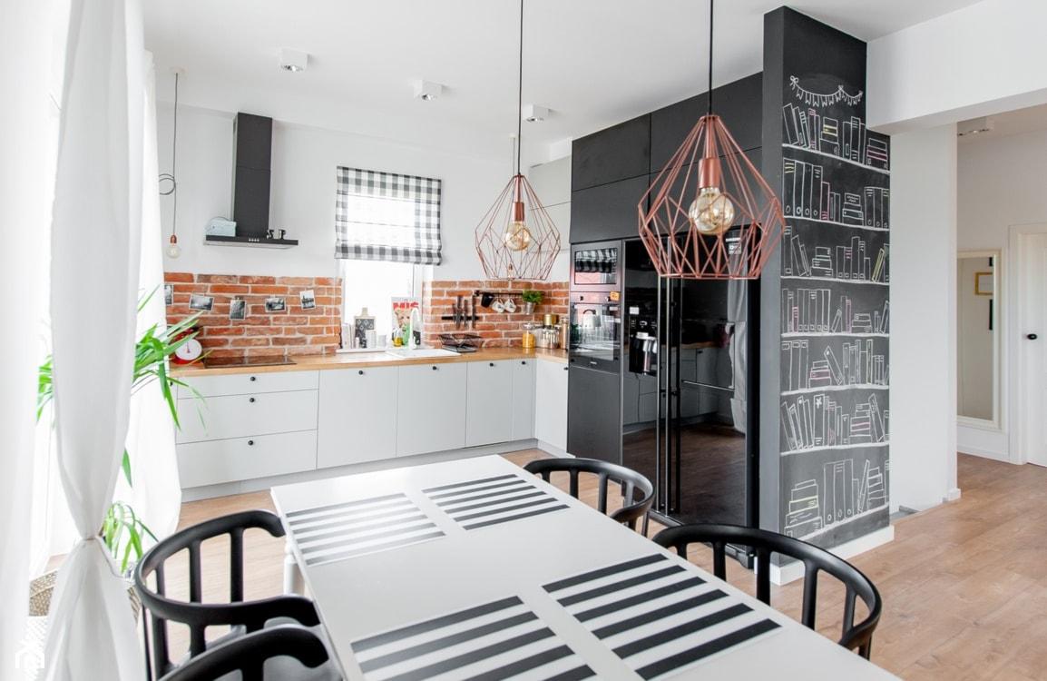 cegła naturalna w kuchni, czarne i białe meble w kuchni, ściana tablicowa w kuchni, industrialne lampy