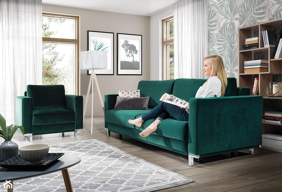 szmaragdowa sofa w salonie, lampa podłogowa z białym abażurem, białe zasłony