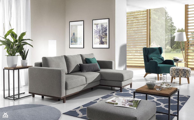szary narożnik, zielony fotel, niebieski dywan, białe zasłony
