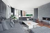 nowoczesny salon, szara sofa, szary kamień ozdobny na ścianie, kominek, drewniana podłoga