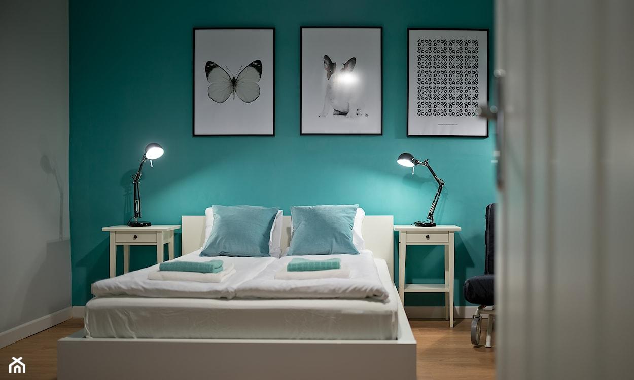turkusowa ściana, grafiki na ścianie, biała pościel, turkusowe poduszki, drewniana podłoga