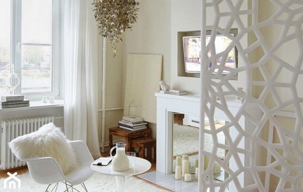 ażurowa ścianka działowa, fotel na biegunach, biały dywan. ozdobny kominek