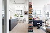 salon oddzielony od kuchni regałem, czarne szafki kuchenne, drewniana podłoga