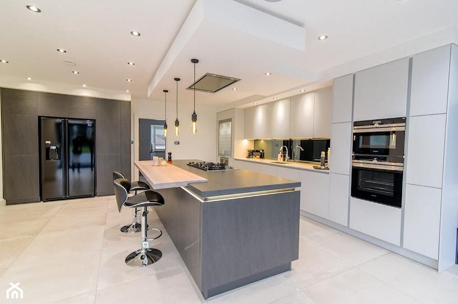 Realizacje - Duża otwarta biała kuchnia z wyspą z oknem, styl nowoczesny - zdjęcie od HOSTA MEBLE