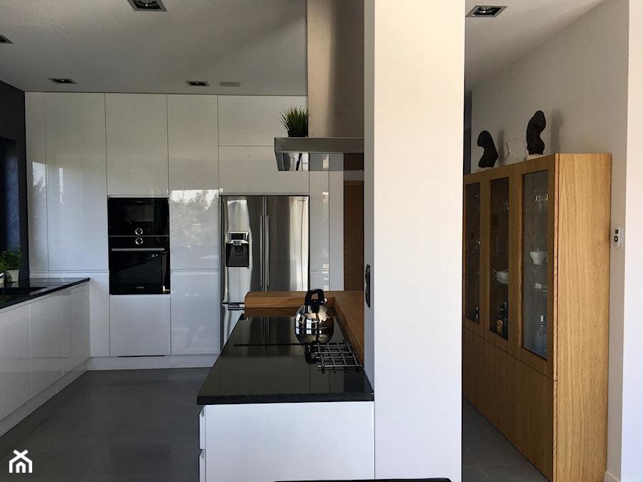 Realizacje - Duża otwarta biała kuchnia w kształcie litery l z wyspą z oknem, styl nowoczesny - zdjęcie od HOSTA MEBLE