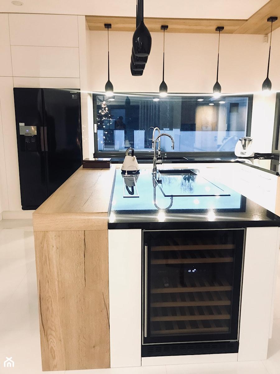 Realizacje - Średnia otwarta biała kuchnia w kształcie litery l z wyspą - zdjęcie od HOSTA MEBLE