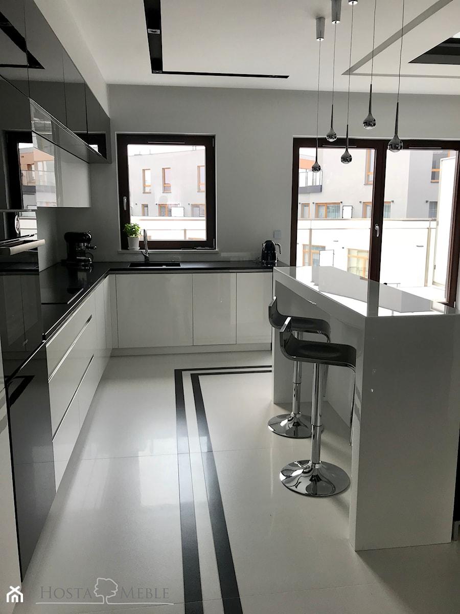 Realizacje - Średnia biała kuchnia w kształcie litery l w aneksie z wyspą z oknem, styl nowoczesny - zdjęcie od HOSTA MEBLE