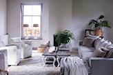 salon w stylu prowansalskim, szara sofa, szary dywan, białe fotel, wiklinowe fotele