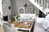 salon w stylu prowansalskim, biała sofa, narzuta w cienkie szare paski, kominek, zegar na ścianie
