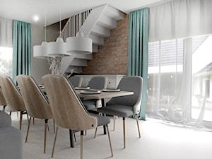 Duży salon z kuchnią i schodami na piętro oraz niebieskimi dodatkami