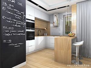 Kuchnia w bieli, drewnie, ściana tablicówka oraz okap tuba