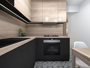 Projekt kuchni w drewnie i czerni z podłoga typu patchwork