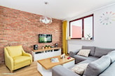 ceglana ściana, szary narożnik, żółty fotel