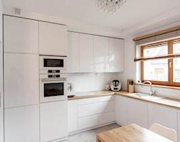 Nowoczesna biała kuchnia z drewnianym blatem - Duża zamknięta biała kuchnia w kształcie litery l z oknem, styl nowoczesny - zdjęcie od pracowniadebina