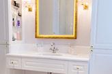 lustro ze złotą ramą, białe meble łazienkowe