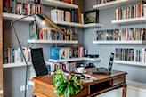 szare ściany, drewniane biurko z ozdobnymi nogami, metalowa lampa podłogowa, białe półki z książkami