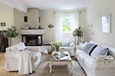 beżowe ściany, biała sofa, kominek w salonie w stylu prowansalskim, stolik z rzeźbionymi nogami