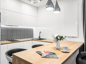 Sesja foto mieszkania na wynajem nr 4_Gdańsk, Wyspa Spichrzów - Mała otwarta biała czarna kuchnia w kształcie litery u w aneksie z oknem, styl minimalistyczny - zdjęcie od WITTWÓRNIA: Robert Witt