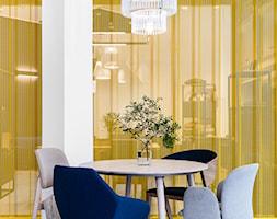 Projekt salonu wyposażenia wnętrz EUFORMA w Gdańsku - Mała otwarta biała żółta jadalnia w salonie jako osobne pomieszczenie - zdjęcie od Marta Koniczuk Pracownia Architektury Wnętrz