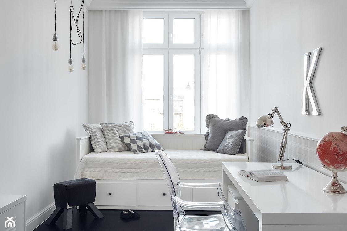 jasny pokój dziecka, białe łóżko, białe biurko, fotel  przeźroczystego tworzywa, metalowa lampa stołowa, czerwony globus