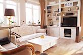 podłoga z jasnego drewna, kremowa sofa z ozdobnym zagłówkiem, lampa podłogowa z szarym abażurem