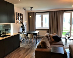 Przytulna elegancja - realizacja projektu salonu z kuchnią na Lipie Piotrowskiej - Mała otwarta beżowa jadalnia w kuchni w salonie, styl nowoczesny - zdjęcie od DekoDeko