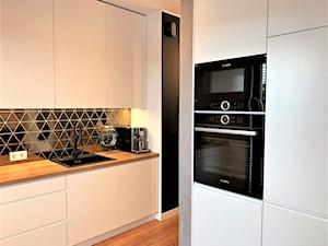 Niewielki dom na Maślicach - realizacja projektu - Średnia zamknięta biała czarna kuchnia w kształcie litery g z oknem, styl nowoczesny - zdjęcie od DekoDeko