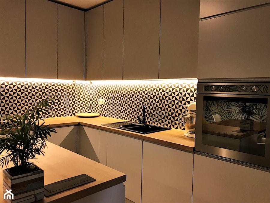 Kuchnia z roślinną tapetą i wielkim stołem - realizacja projektu - Średnia wąska biała czarna kuchnia w kształcie litery l, styl nowoczesny - zdjęcie od DekoDeko