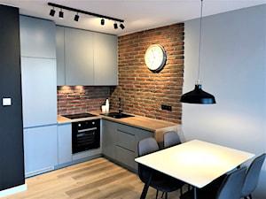 Realizacja - oryginalne mieszkanie na wynajem - Mała brązowa kuchnia w kształcie litery l w aneksie, styl nowoczesny - zdjęcie od DekoDeko