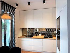 Niewielki dom na Maślicach - realizacja projektu - Mała otwarta biała szara czarna kuchnia w kształcie litery l w aneksie z oknem, styl nowoczesny - zdjęcie od DekoDeko
