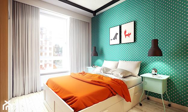 zielona ściana w kropki i białe łóżko z pomarańczową narzutą
